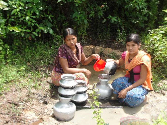 Two women of Khebukpara village in Bandarban Sadar upazila collect water from a well for cooking and drinking as there is no arrangement for pure water in the area. PHOTO: STAR