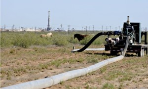 Large hoses run from hydraulic fracturing drill sites in Midland, Texas. Fracking uses huge amounts water to free oil and natural gas trapped deep in underground rocks. With fresh water not as plentiful, companies have been looking for ways to recycle their waste. Photo Credit: Pat Sullivan