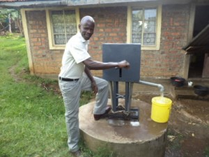 Innovation: Wycliffe Churchill pumps water from fabricates water pump in his village home in Kamagambo village in Migori County. He innovated the pump after being disturbed to see locals succumb to water-borne diseases because of lack of clean drinking water. [Photo credit: HEZRON OCHIEL/STANDARD]