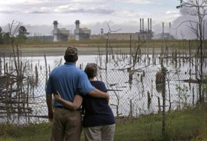 In this April 25, 2014 photo, Bryant Gobble, left, hugs his wife, Sherry Gobble, right, as they look from their yard across an ash pond full of dead trees toward Duke Energy's Buck Steam Station in Dukeville, N.C.  (Photo credit: AP Photo/Chuck) Burton
