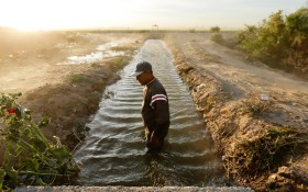 Abelardo Martinez in a blocked duct that leads water to his fields near Colonia Coahuila, Mexico, through a maze of canals stemming off the Colorado River, in March 2014. After a landmark agreement between the U.S. and Mexico, water has begun pouring through the Colorado River Delta again. (Photo credit: Gregory Bull/AP)