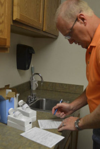 (Photo credit: Lorene Parshall/Herald Times)  Chuck Edwards, environmental health inspector, demonstrates the process necessary to have well water tested for contaminating bacteria and chemicals.