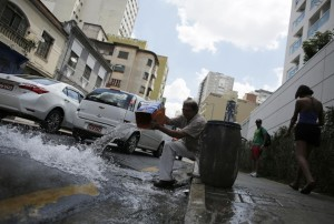 A man pours excess water on to the street after filling up his barrel with water from a spout near the construction site of a building in São Paulo, Feb. 3, 2015. Builders opened a water well by drilling into one of the numerous rivers running underneath the city, according to local media. Residents and small businesses took advantage of the water as São Paulo, Brazil's largest city, has nearly run out. (Photo credit: Reuters)