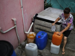A woman fills a bucket with rainwater she collects from a water box for use in the bathroom and to clean the floor of her house in Brasilandia slum, São Paulo, Feb. 10, 2015. Brazilians are hoarding water in their apartments, drilling homemade wells and taking other emergency measures while the government rations water. (Photo credit: Reuters)