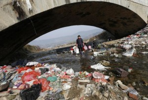 Villagers wash clothes in the garbage-filled Shenling River in China's Anhui province on Feb. 14, 2015. (Photo credit: Reuters/William Hong)