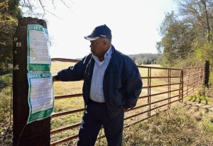 Alfonzo Wherry looks at notices posted outside a field in Chester County, S.C., where sewage sludge from Charlotte was to be sprayed. Neighbors complained that the sludge causes asthma attacks, headaches and other health problems.  (Photo credit: Jeff Siner)